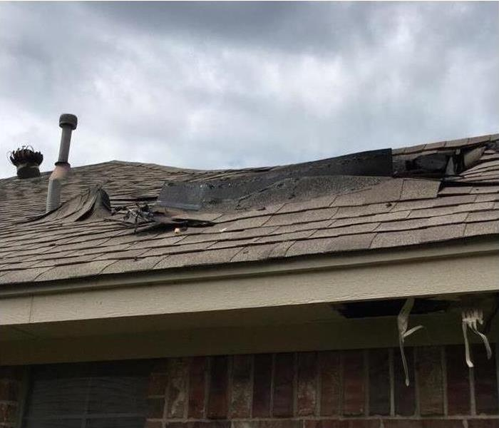 roof shingles on a house peeling back from fire damage