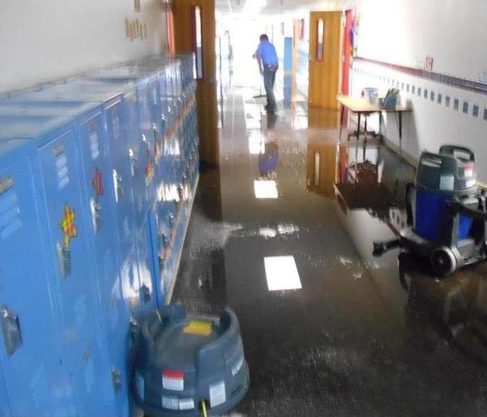 water flooding the floor of a school hallway